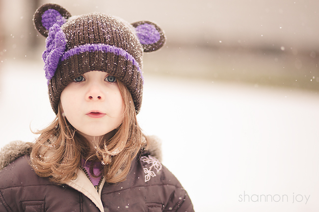 Photograph of a child in the snow wearing a brown hat with purple ears