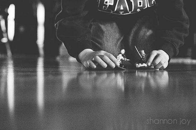Black and white photograph of a child playing with toys.