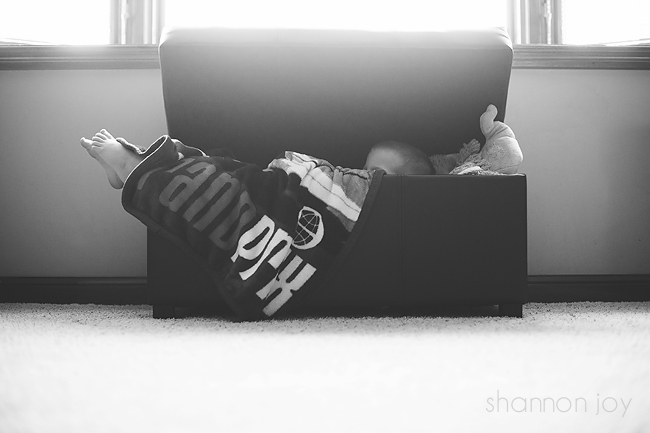 Black and white photo of a child laying in a toy box in front of a bright window during project 365