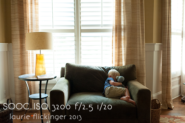 child snuggling animal on chair with windows behind him