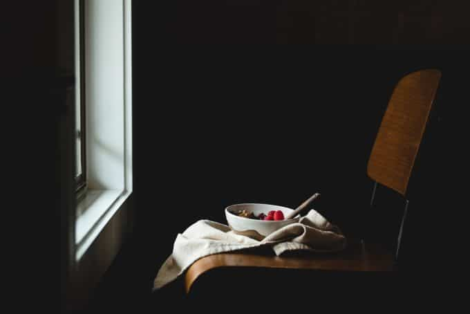 White bowl of fruit in a dark room with window light coming in to show still life photography