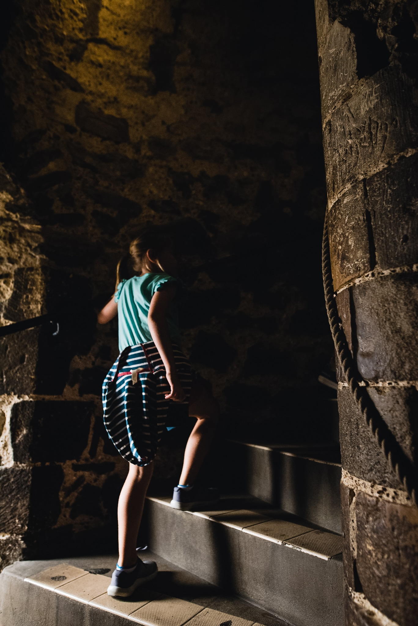 child walking up castle stairs in low light