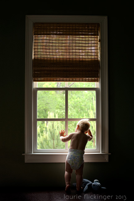 child framed in window light looking out window