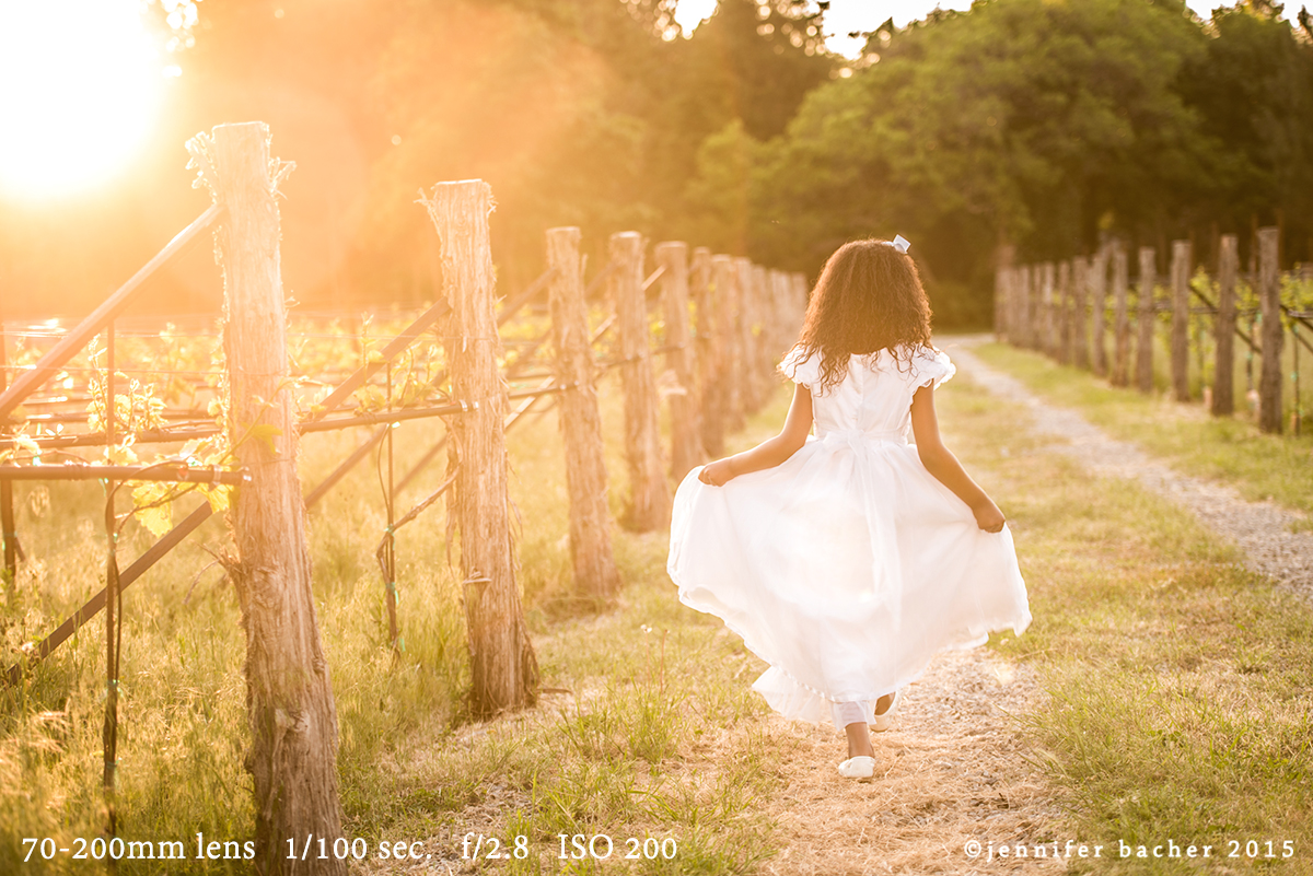 Child walking away from camera in a white dress. A sun flare is in the top left corner.