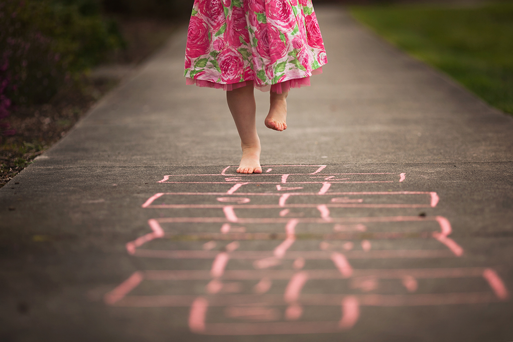 child playing hopscotch with sidewalk acting as a leading line