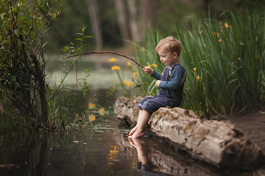 boy sitting on log fishing with stick with log as leading line
