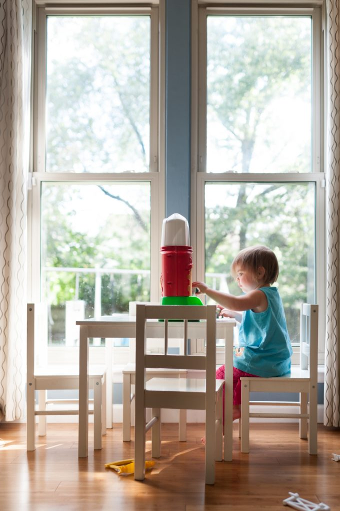 Child playing with toy in front of bright window for example of candid photography style