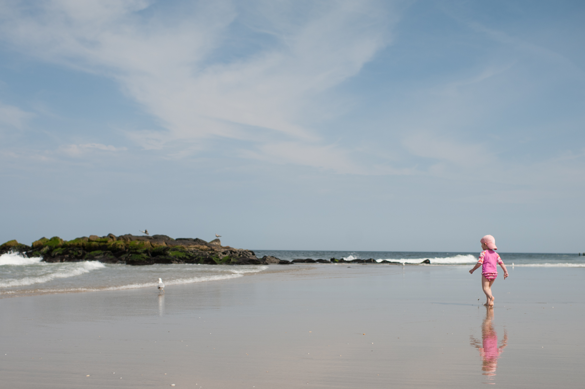 A child wearing a pink bathing suit is walking on the beach out toward a bird.