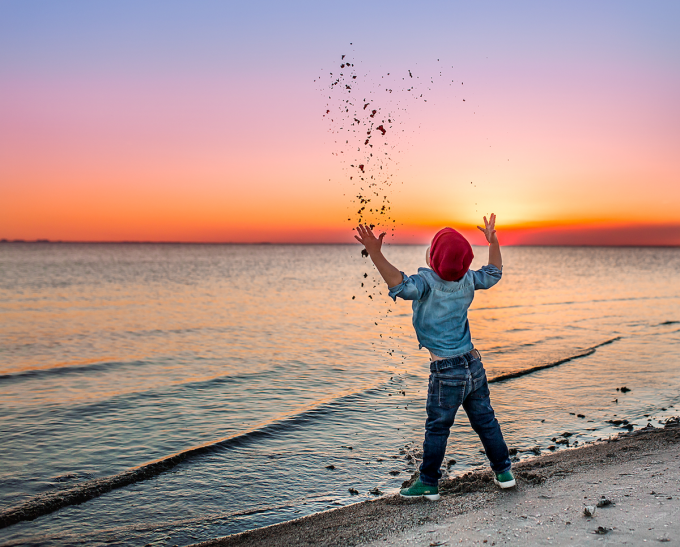 Child throwing sand on beach and freezing the motion