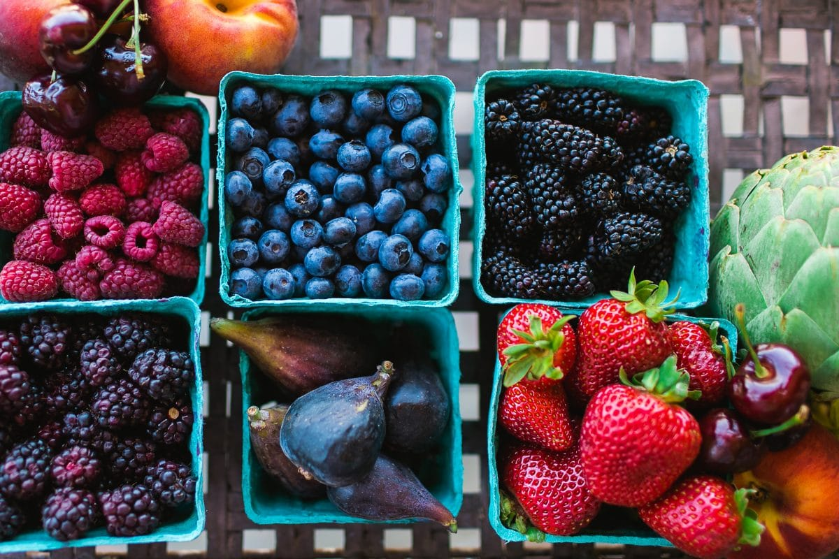 Different berries in blue containers on a table.