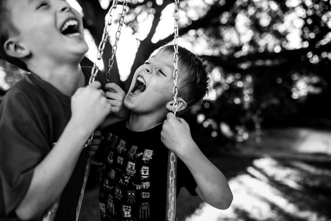 boys on tire swing in candid photography photo