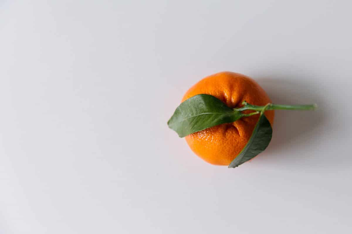 An orange on a white table with two green leaves.