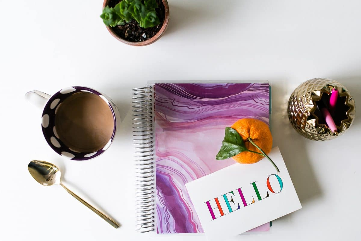 Still life image of a purple marbled planner, a cup of coffee, two plants, a greeting card and an orange on a table.