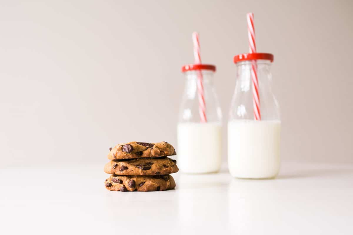 Three chocolate chip cookies and two jars of milk with red and white straws.