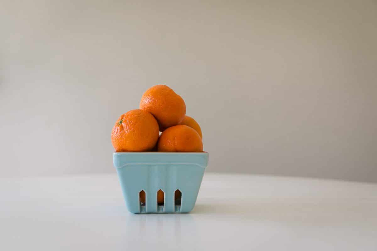 Oranges stacked in a blue container on a white table