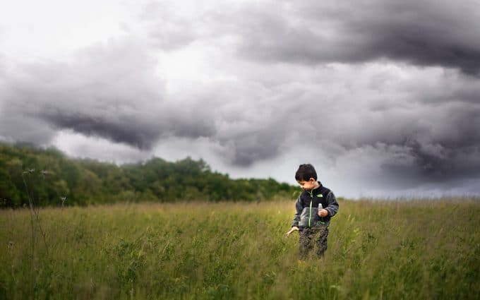boy in field before a storm surrounded by space for a minimalist photo