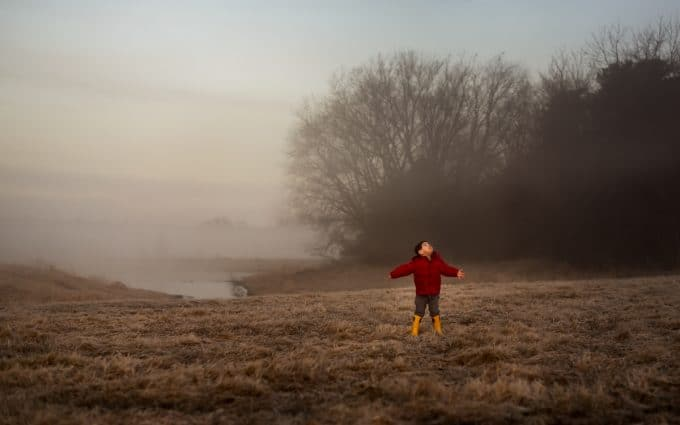child in red coat in field of fog for minimalist photo