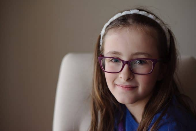A child wearing purple glasses smiling at the camera. She has tack sharp eyes as the focus was placed to avoid a blurry photo.