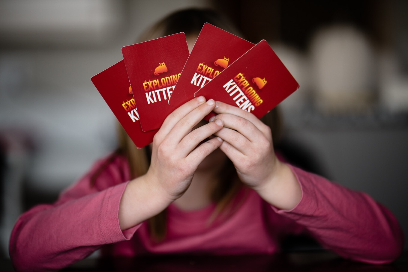 child hands holding exploding kittens cards