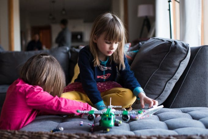 Image of children playing with airplane toy sitting on a couch. Lifestyle photography style