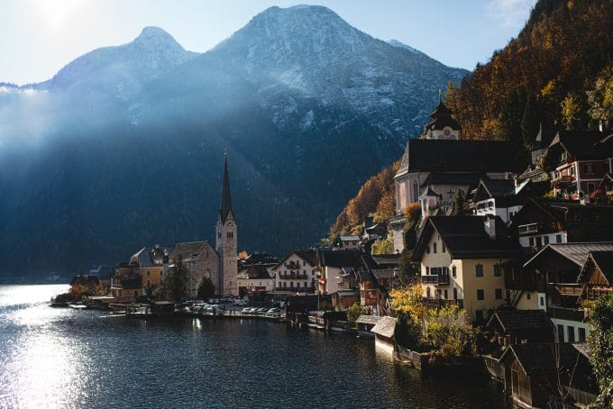 Image of a quaint European village next to lake and mountains to show travel photography style