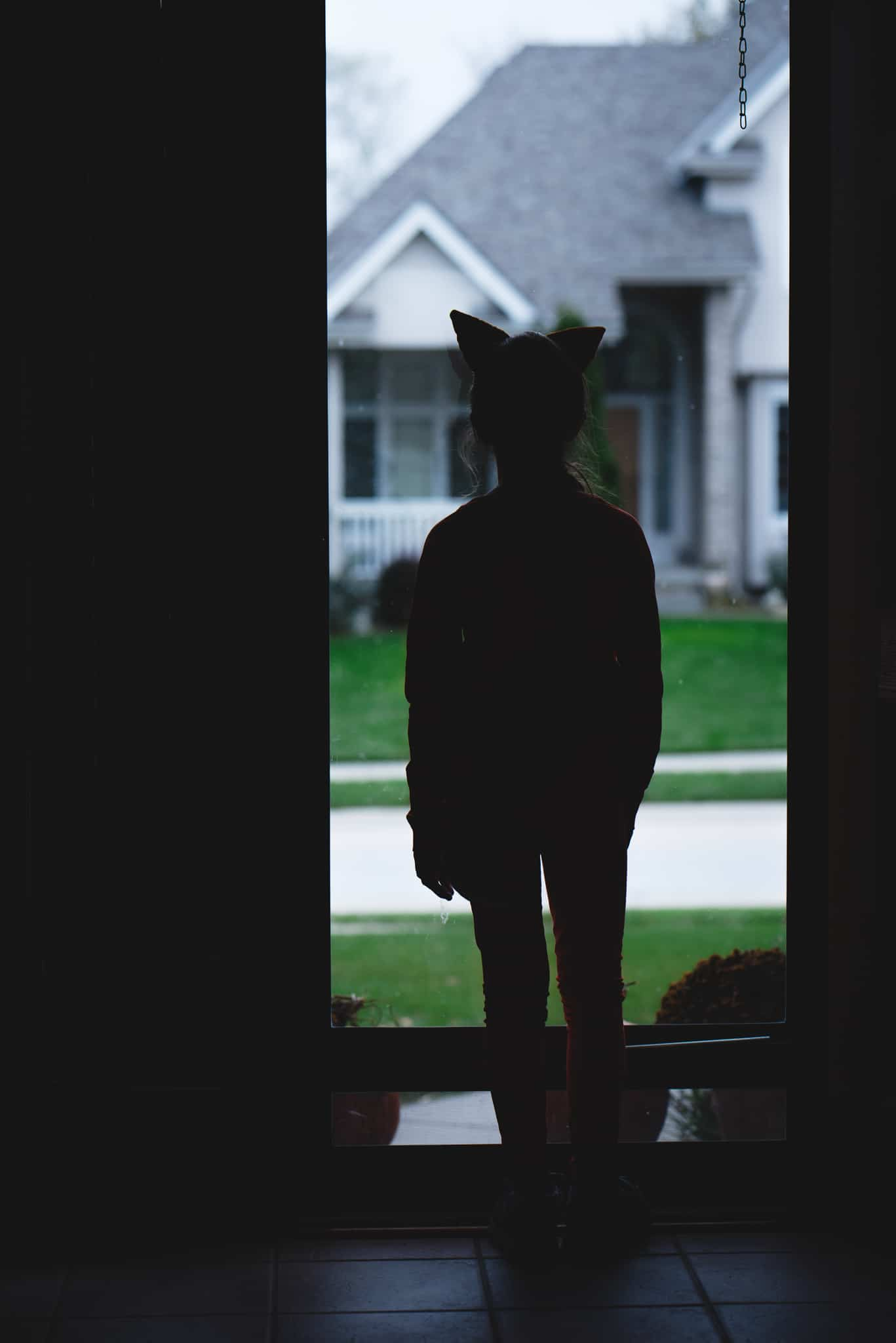 Child in fox costume standing in front of glass door creating a silhouette