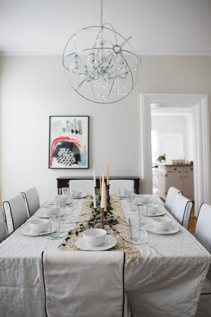 Dining room set up with a white table cloth and dishes set on top. Shows perfect white balance
