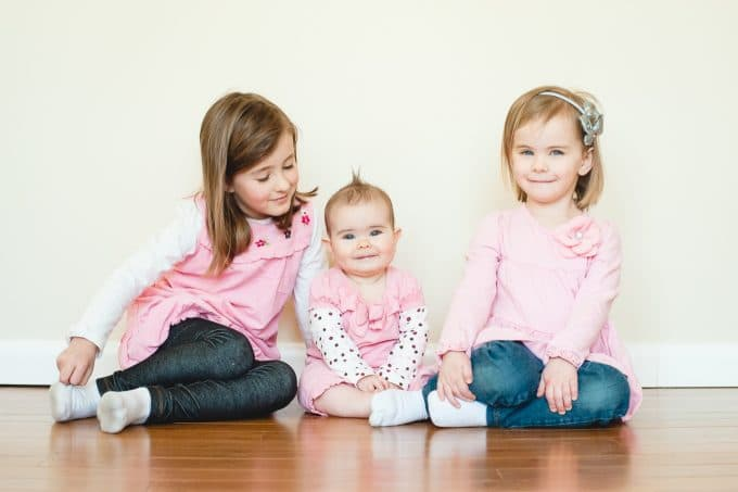 Three children wearing pink sitting on the floor all smiling with correct white balance.