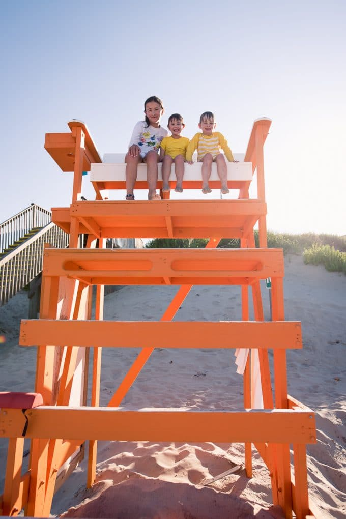 3 children sitting on an orange life guard stand on the beach. The sun is coming in behind them creating a backlit photograph.