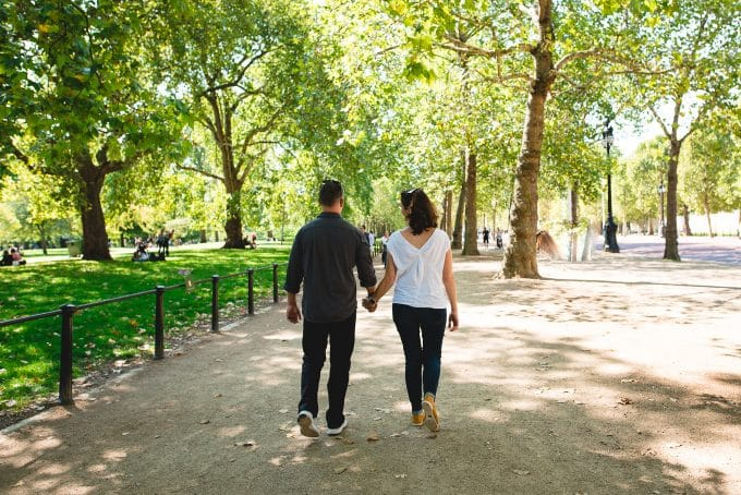 Image of couple holding hands and walking through a park.