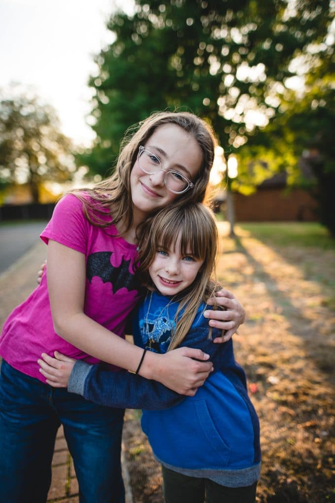 Two children hugging one is a pink shirt, one in a blue shirt. Nice bokeh coming in through the trees in the background. Backlighting photography during golden hour.