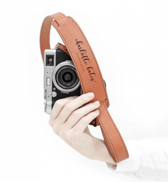 Light tan personalized camera strap and black camera being held by a hand to show gifts for photographers.