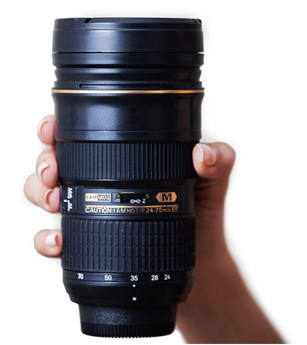 A hand holding a tall black camera lens look a like. This mug is a great gift for photographers.