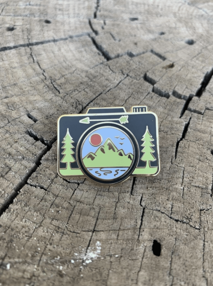 A small black pin that is in the shape of a camera. It has trees and a mountain scene.