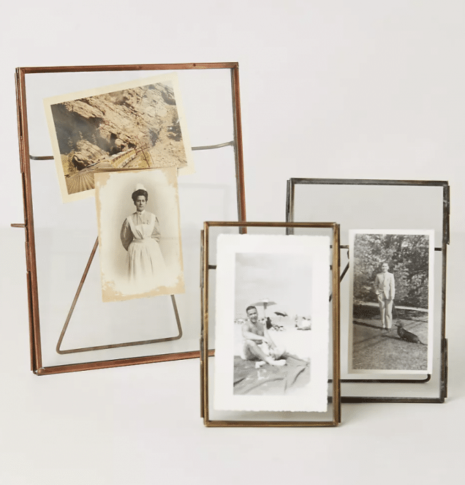 3 metal and glass picture frames holding antique photographs.