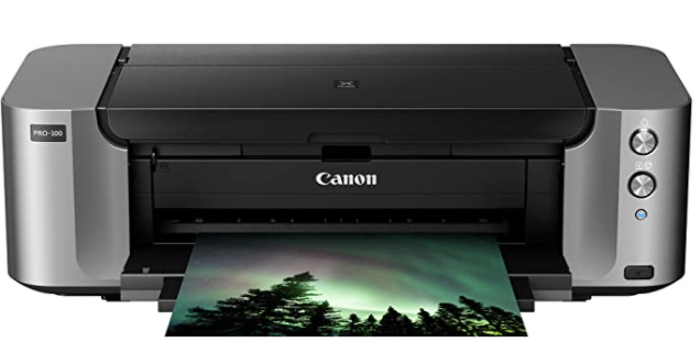 Black and gray photo printer with a silhouette image of trees amongst a green night sky.