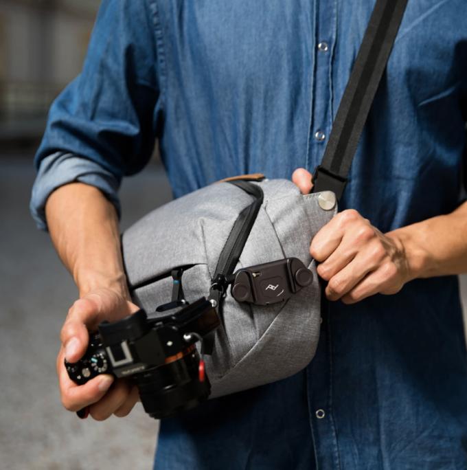 A gray camera bag holding a black camera clip and a man holding a black camera.