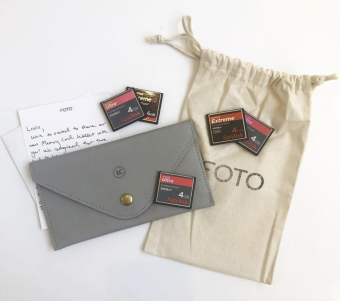 A tan bag with the word FOTO on it. 5 small red and balck SD cards. A white letter and a gray leather sd card wallet.