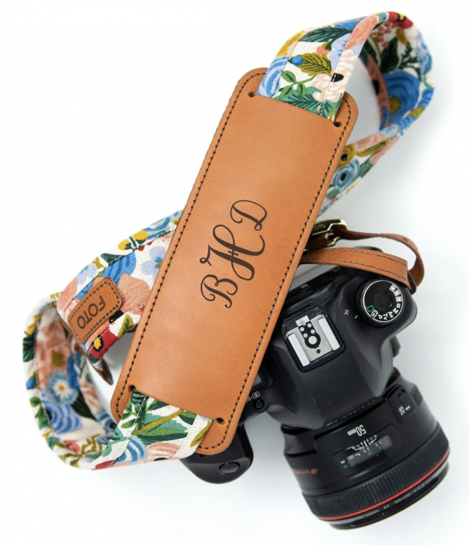 Floral camera strap with a light brown leather strap with the initials BHD on a black camera.
