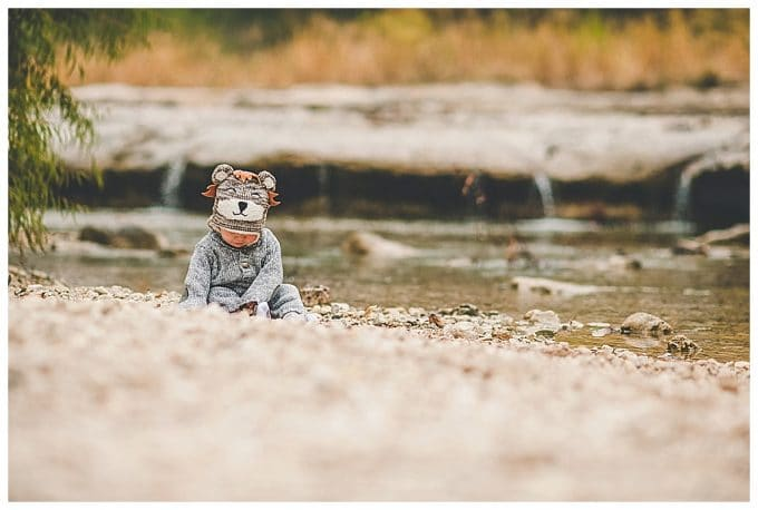 Photo of child sitting by a river.