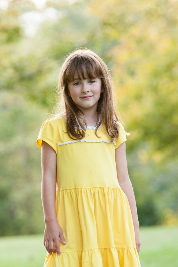 Image of child wearing a yellow dress with a very blurred background showing an example of how to use aperture for portraits.