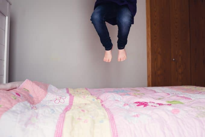 Child jumping on pink bed. Motion was caught by high shutter speed it is not a blurry photo even though there is movement.