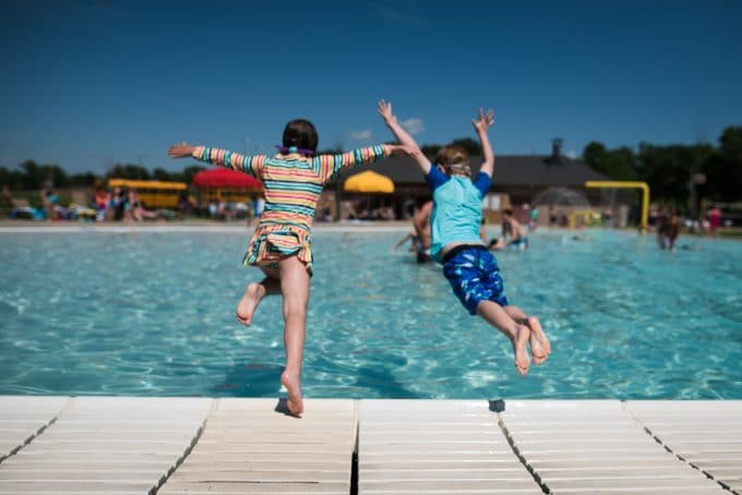 Two children jumping into a pool. It is not a blurry photo because the shutter speed was high enough to catch the motion.