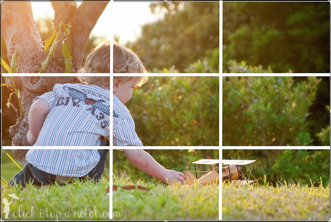 Child playing with airplane with a grid overlay on the top of the image to demonstrate a rule of composition in photography called rule of thirds.