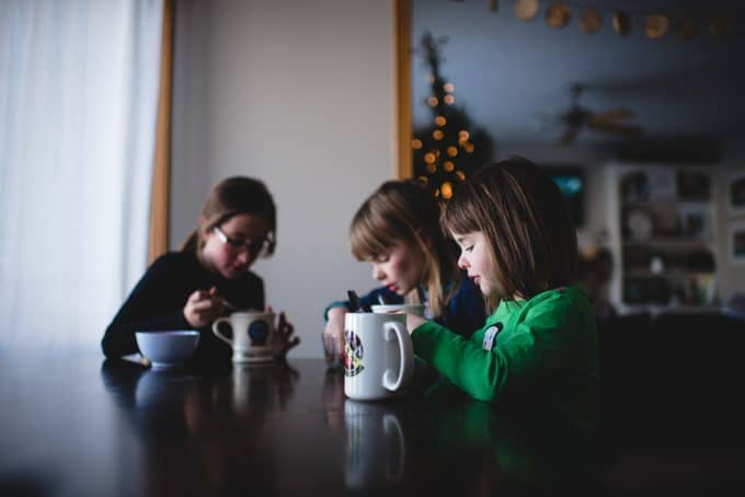 photo of 3 children at a table with mugs and the christmas tree in the background.