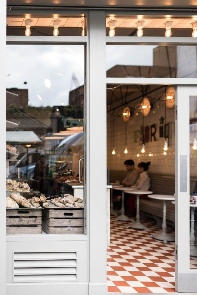 Photo taken from outside of a cafe looking in. Two people are sitting at a table and there is fresh bread in the window.