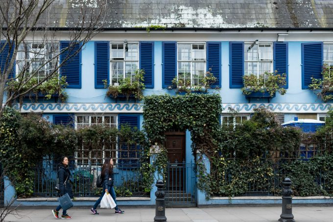 Two people carrying bags walking in front of a blue house with dark blue shutters.