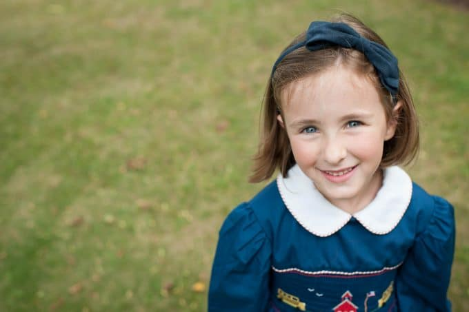A child wearing a blue school dress with the focal point on her eyes.