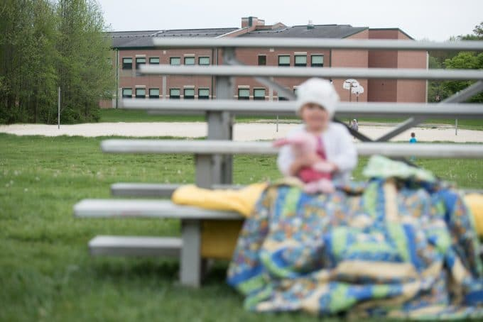 Child sitting on bleachers wrapped in blankets holding piglet. Focal point on the background.