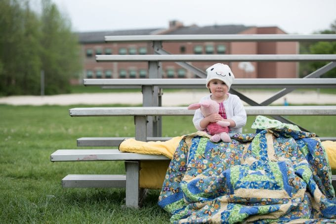 Child sitting on bleachers wrapped in blankets holding piglet. Focal point on child.